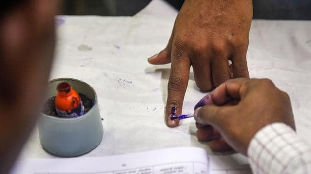 A polling official applies indelible ink on the finger of a voter at a polling station.(PTI Photo)