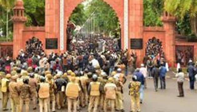 Police personnel stand guard outside Aligarh Muslim University (AMU) as students protest against the passing of Citizenship Amendment Bill, in Aligarh(PTI)