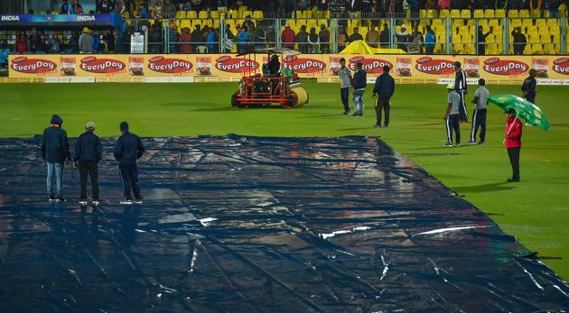 Groundsmen cover their pitch due to rain.(PTI)