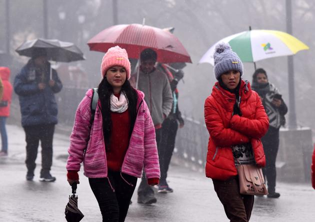 Locals and tourists making their way through light rain on The Ridge in Shimla on Monday.(Deepak Sansta /HT)