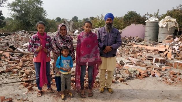 Surendra Singh with his wife and three daughters amid the debris of their house that was demolished by the administration in the tribal-dominated Karahal tehsil of Sheopur district on the Madhya Pradesh-Rajasthan border in December-end.(HT Photo)
