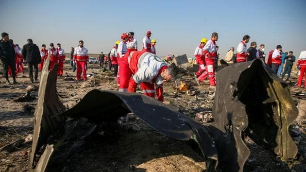 Red Crescent workers check the debris from the Ukraine International Airlines plane, that crashed after take-off from Iran's Imam Khomeini airport, on the outskirts of Tehran, Iran January 8, 2020.(West Asia News Agency via Reuters)