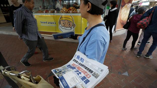 "A vendor gives out copies of newspaper with a headlines of ""Wuhan break out a new type of coronavirus, Hong Kong prevent SARS repeat"" at a street in Hong Kong, Saturday.(AP Photo)"