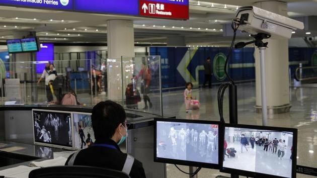 A health surveillance officer monitors passengers arriving at the Hong Kong International airport in Hong Kong.(AP Photo)