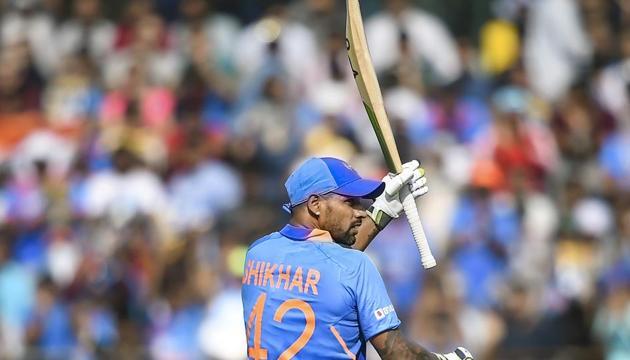 Indian batsman Shikhar Dhawan raises his bat after scoring fifty runs during the first one day international (ODI) cricket match between India and Australia, at the Wankhede Stadium in Mumbai, Tuesday, Jan. 14, 2020(PTI)