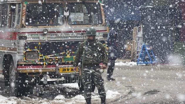 An Indian paramilitary soldier stands guard as snow falls in Srinagar.(AP)