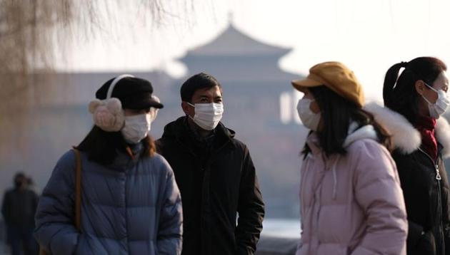 People wearing protective masks walk outside Forbidden City which is closed to visitors, according to a notice in its main entrance for the safety concern following the outbreak of a new coronavirus, in Beijing, China on January 25, 2020.(Reuters Photo)