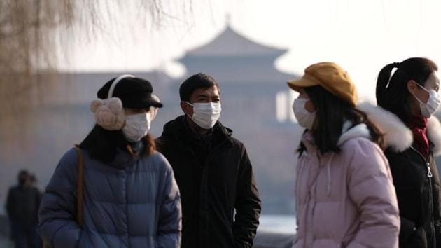 People wearing protective masks walk outside Forbidden City, which is closed to visitors, following the outbreak of coronavirus, in China.(Reuters image)