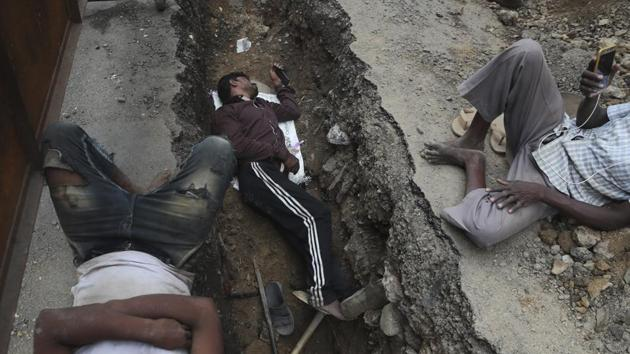 A laborer watches a movie on his mobile phone as he takes a break with others as they repair a road in Mumbai.(Photo: AP)