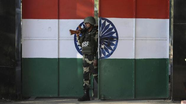 An Indian Border Security Force soldier walks through a gate painted with the Indian flag at the India-Pakistan border.(AP)