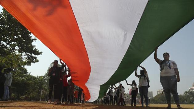 Students hold a national flag, claimed to be more than 1,000-feet long, during a rally ahead of Republic Day in Mumbai.(Photo: AP)