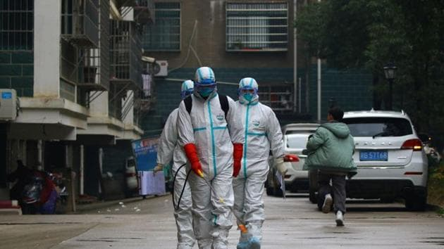 Workers from local disease control and prevention department in protective suits disinfect a residential area following the outbreak of a new coronavirus, in Ruichang, Jiangxi province, China.(REUTERS)