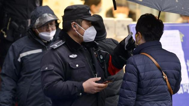 A policeman wearing a face mask takes a tourist's temperature at the Qinhuai scenic zone in Nanjing in eastern China's Jiangsu province. The virus-hit Chinese city of Wuhan, already on lockdown, has banned most vehicles downtown.(AP PHOTO.)