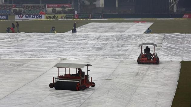 Ground staff work to dry the pitch and field following a light rain at Gaddafi stadium, in Lahore.(AP)