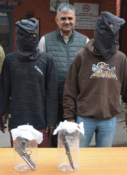 The accused along with seized weapons in police custody.(SANT ARORA/HT)