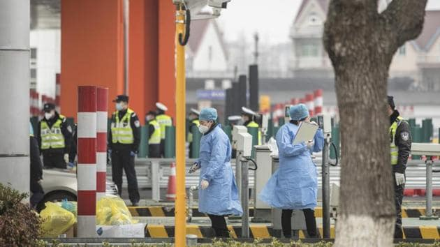 Wuhan Coronavirus: Masked health professionals and police officers stand at a screening checkpoint on a highway toll station on the outskirts of Shanghai, China.(Bloomberg)