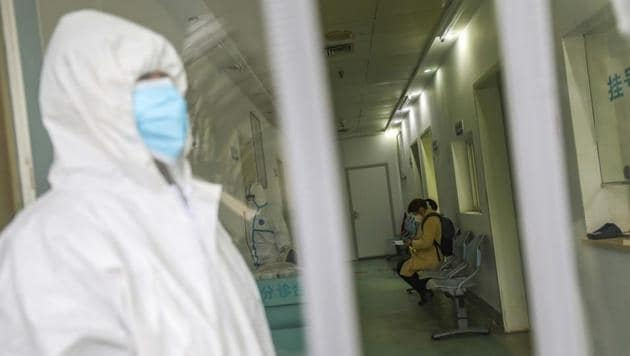 Wuhan: Medical workers in protective gear stand as a woman suspected of being ill with coronavirus waits to be seen at a community health station in Wuhan in central China's Hubei Province, Monday, Jan. 27, 2020.(AP)
