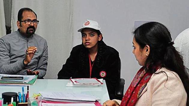 Class 12 student Sana Siddiqui (centre) at the office of Ghaziabad CDO Asmita Lal (right).(Sakib Ali /HT photo)