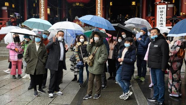 Tourist wearing face masks gather in front of the Sensoji temple in the Asakusa district of Tokyo, Japan, on Tuesday. Japan is making arrangements with the Chinese government for chartered flights to repatriate Japanese from Wuhan in response to the novel coronavirus outbreak.(Bloomberg Photo)