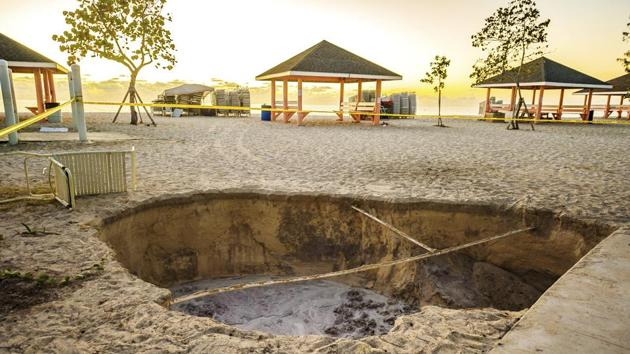 A sinkhole is surrounded by police tape after it appeared when a powerful magnitude 7.7 earthquake struck in the Caribbean Sea between Jamaica and eastern Cuba on Jan. 28, 2020.(AP)