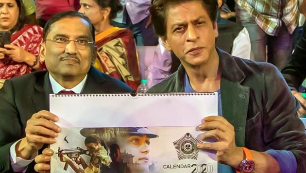 Mumbai: A copy of the Mumbai Police Calendar being presented to Bollywood superstar Shah Rukh Khan at the grand event Umang in Mumbai.(IANS)