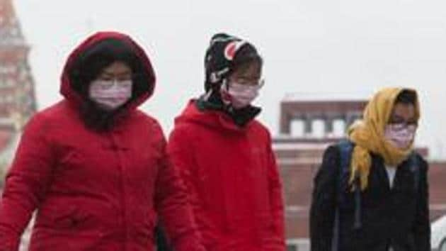 Tourists wear protective face masks as they walk in Red Square near the Kremlin in Moscow on Tuesday, January 28.(Bloomberg)