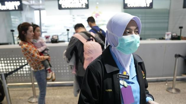 A health official hands out information about the current coronavirus at the Kuala Lumpur International Airport in Sepang, Malaysia.(AP)