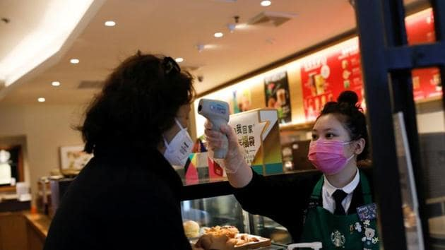 A worker uses a thermometer to check the temperature of a customer as she enters a Starbucks shop as the country is hit by an outbreak of the new coronavirus, in Beijing.(REUTERS)