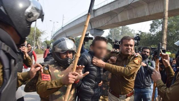 Police detain an unidentified person after he opened fire towards students protesting against the Citizenship Amendment Act, near Jamia Millia Islamia University, in New Delhi, on Jan. 30, 2020.(PTI)