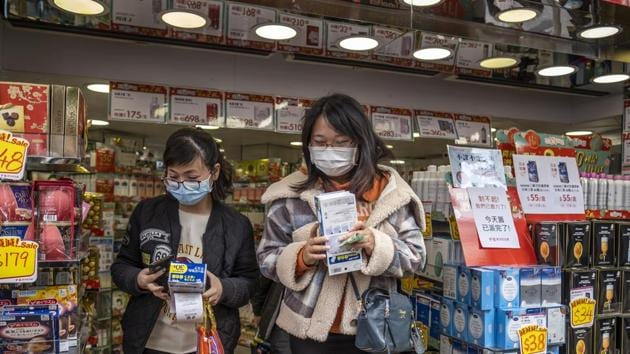 Customers leave with boxes of newly purchased protective masks at a Bonjour Holdings Ltd. store in Hong Kong, China.(Bloomberg)