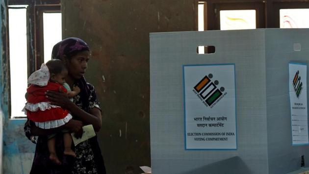 A voter, carrying her son, casts her vote during the repolling at Daryaganj, in Delhi.(Amal KS/HT PHOTO)