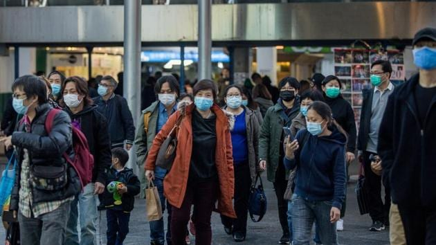 Pedestrians wearing masks walk out of a ferry pier terminal in the Tsim She Tsui district in Hong Kong, China.(Bloomberg)