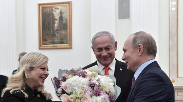 Russian President Vladimir Putin, right, greets Israeli Prime Minister Benjamin Netanyahu's wife Sara, left, as Israeli Prime Minister Benjamin Netanyahu stands in the center prior to their talks in the Kremlin in Moscow, Russia, Thursday, Jan. 30, 2020. Netanyahu visited Moscow to discuss the U.S. Mideast peace plan with Putin and take an Israeli woman who had been jailed in Russia back home.(AP)