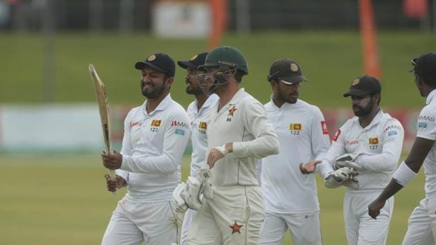 Sri Lanka and Zimbabwe players share a light moment as they walk off the pitch during their test match at Harare Sports Club.(AP)