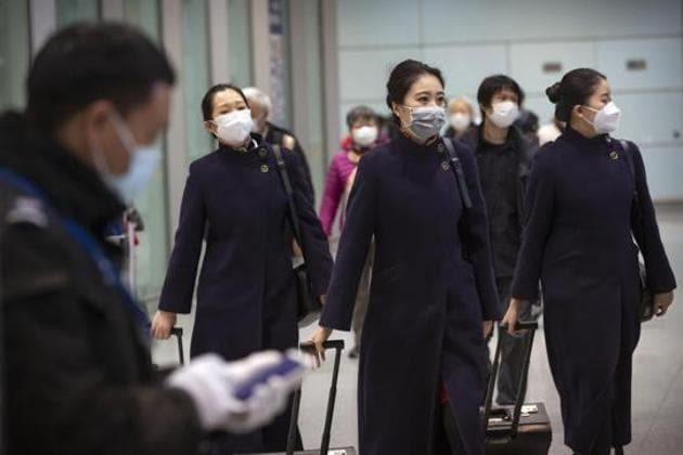 Flight crew members wearing face masks walk through the international arrivals area at Beijing Capital International Airport on January 30.(AP)