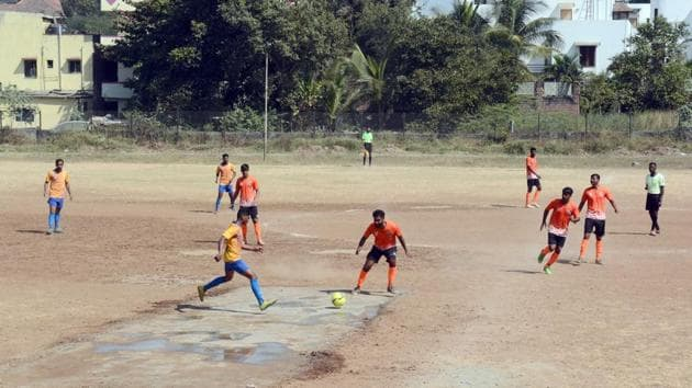 Central Railways (yellow) play Pune Police at the Dobarwadi ground on Thursday, with a cement patch in the centre.(Shankar Narayan/HT PHOTO)