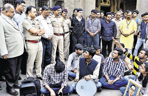 Ravindra Pardeshi (left), principal, Fergusson College and police personnel, attempt to reason with the protesting students.(Ravindra Joshi/HT PHOTO)