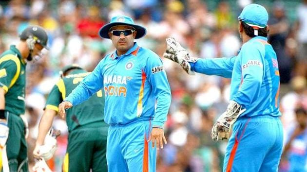 MS Dhoni (R) and teammate Virender Sehwag discuss fielding options while playing against Australia in their one day international cricket match in Sydney.(AP)