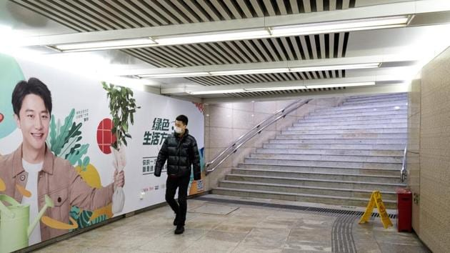 A pedestrian wearing a protective mask walks through a tunnel in Beijing, China, on Sunday, Feb. 2, 2020.(Bloomberg)