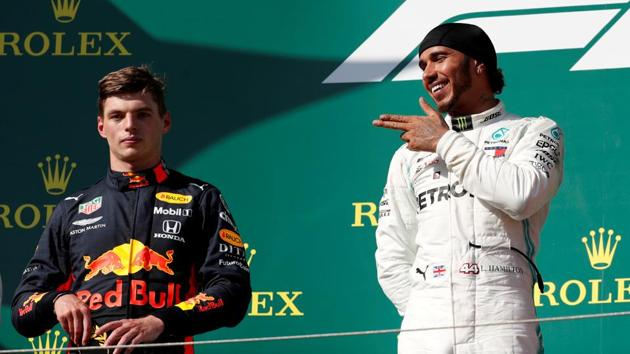 Mercedes' Lewis Hamilton gestures on the podium as he celebrates winning the Hungarian Grand Prix as Red Bull's Max Verstappen looks on.(REUTERS)