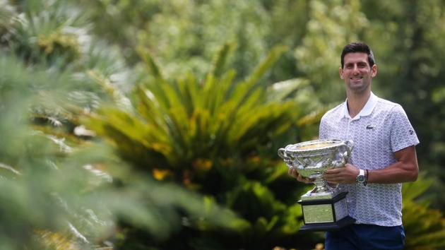 Australian Open champion Serbia's Novak Djokovic poses with the trophy during a photo shoot at the Royal Botanic Gardens Victoria.(REUTERS)
