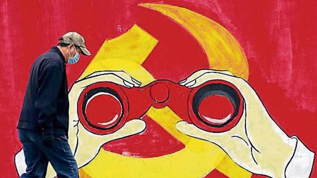 A man walks past a mural showing a modified image of the Chinese Communist Party emblem in Shanghai.