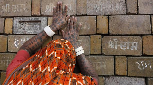 """A woman devotee prays to the bricks reading """"Shree Ram"""" ( Lord Ram), which are expected to be used in constructing the Ram temple, in Ayodhya.(AP)"""