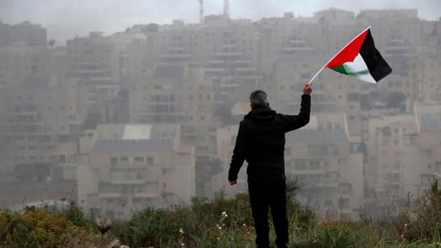 A demonstrator holds a Palestinian flag as the Jewish settlement of Modiin is seen in the background, during a protest against the U.S. President Donald Trump's Middle East peace plan, in the village of Bilin in the Israeli-occupied West Bank February 7, 2020.(REUTERS)