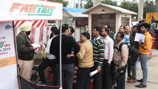 People in the process of purchasing FASTags from the NHAI booth(Vipin Kumar /HT PHOTO)