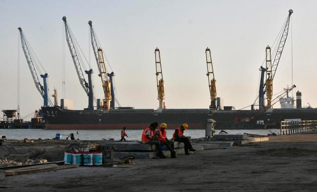 Worker rest in front of a cargo ship at a port in Gujarat.(Reuters File Photo)