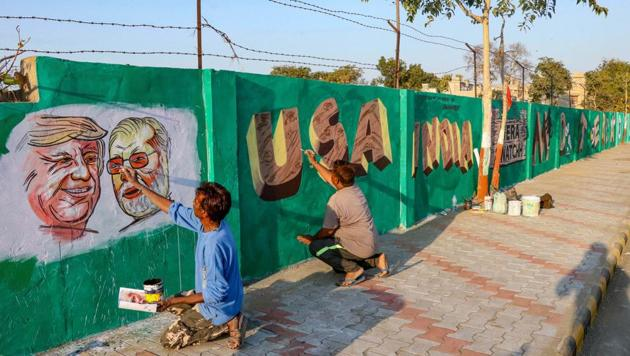 A man gives finishing touches to paintings of US President Donald Trump and Prime Minister Narendra Modi on a wall as part of a beautification along a route that Trump and Modi will be taking during Trump's upcoming visit, in Ahmedabad.(PTI Photo)