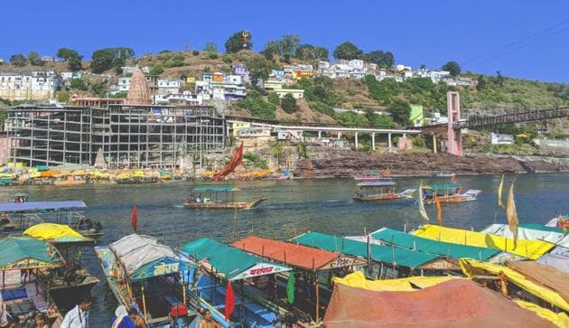 Devotees from near and far hustle to get a glimpse of the sacred rock on the Sanskrit OM shaped island of Mandatha. The free-flowing river is put in check by a concrete dam, yet it flows unabashed washing the sins of the devotees who have flocked on its ghats.