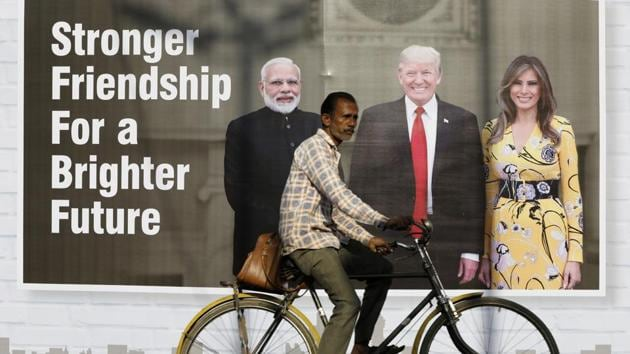 A man rides his cycle past a hoarding with the images of PM Narendra Modi, Donald Trump and first lady Melania Trump ahead of US president's visit, in Ahmedabad, India, February 22, 2020.(Reuters photo)