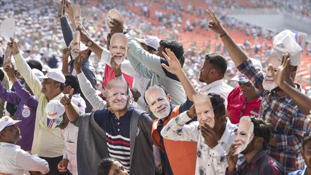 People wearing Prime Minister Narendra Modi and U.S. President Donald Trump's mask wave as they arrive to attend the 'Namaste Trump' event at Sardar Patel Motera Stadium, in Ahmedabad(PTI)